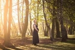 Zwangere vrouw 's ochtends bij het eerste zonlicht in een bos